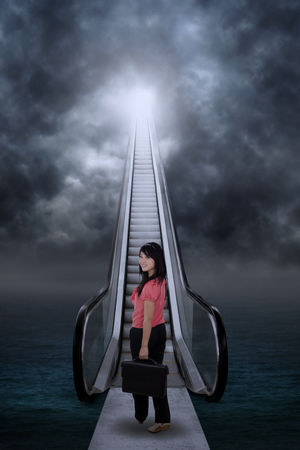 Asian businesswoman standing by the escalator on the sea Stock Photo