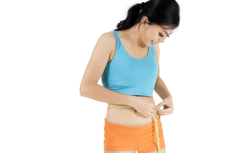 Picture of young woman measuring her slim waistline, isolated on white background Stock Photo