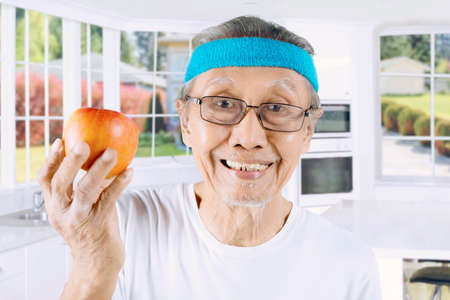 Closeup of old man smiling at the camera while showing a fresh apple in the kitchen Stock Photo