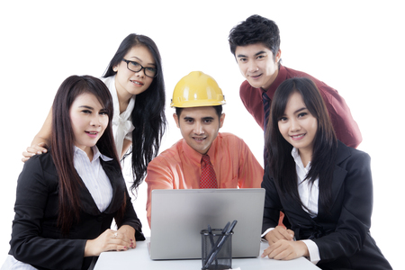 Young engineer and business people working with a laptop while smiling at the camera, isolated on white background Stock Photo