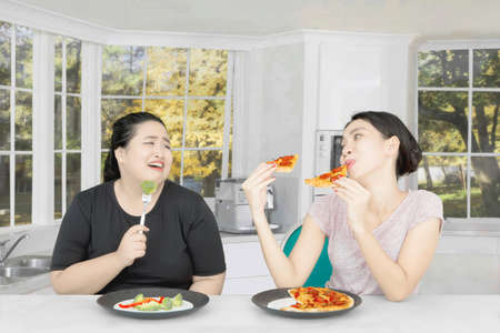 Image fat woman looks sad while eating salad and looking at her friend with pizza. Shot in the kitchen Stock Photo