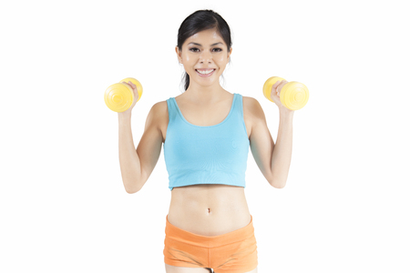 Sporty woman lifting two dumbbells while smiling at the camera, isolated on white background