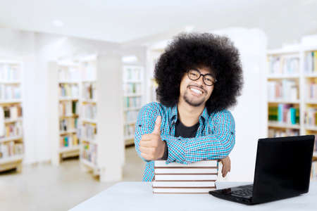 Image of Afro male college student studying with a pile of books and laptop while showing thumb up in the library