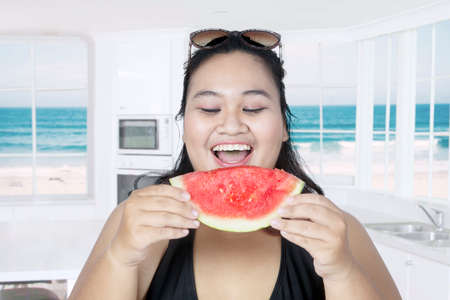 Obese woman eating fresh watermelon with beach background on the window