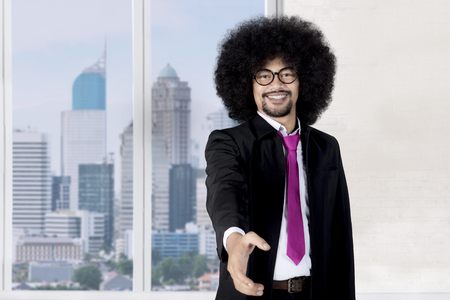 Image of Afro businessman offering a handshake while standing near the window