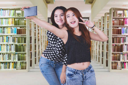 Image of two Asian female students using a mobile phone to take selfie photos while standing in the library
