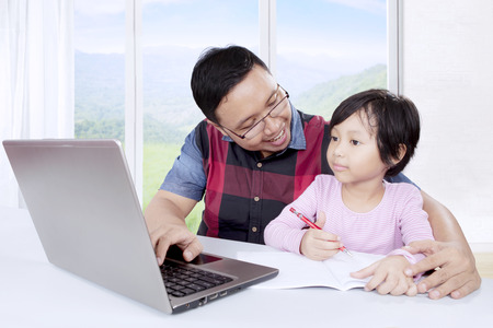 Cute little girl learning to write while using a laptop with her father and sitting near the window