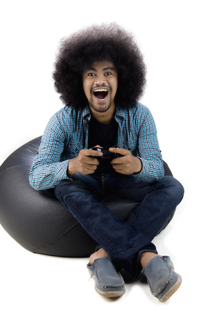 Portrait of African man playing video game with expression win, isolated on white background