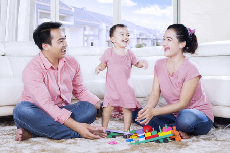 living room window: Picture of cute girl is dancing and playing with her parents while laughing together in the living room