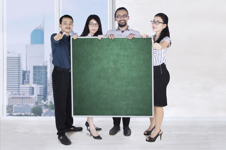 Group of young multiracial business people showing thumbs up while holding a blank blackboard in the office Stock Photo