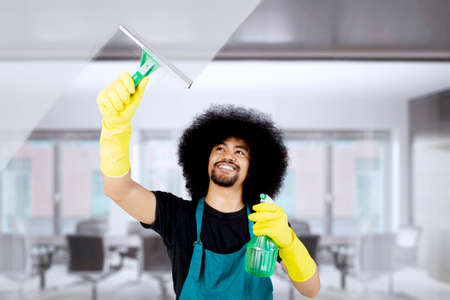 Photo of African maid cleaning a mirror with a spray and squeegee while standing in the office