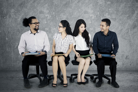 Group of young multiracial worker candidates chatting to each others while waiting for job interview Stock Photo