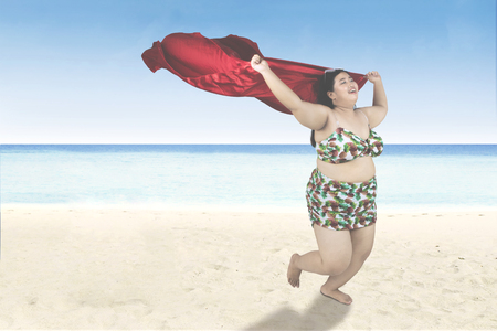 Joyful obese woman wearing bikini and running on the beach while holding a red scarf