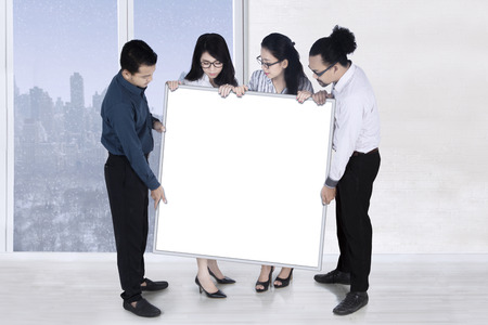 Group of young multiracial business people presenting empty banner in the office