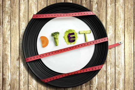 dietology: Top view of diet text made of slices healthy vegetable and a plate tied up with measure tape above wooden table