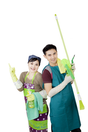 Picture of cheerful young couple wearing apron while holding cleaning supplies, isolated on white background