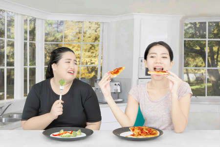 Asian woman eating pizza while disturbing her friend for diet and sitting together in the kitchen