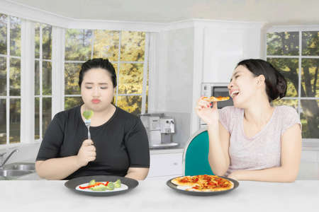 Young woman eating pizza while mocking her fat friend eat salad and sitting at home