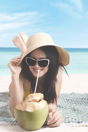 Portrait of pretty female wearing a hat while drinking coconut water and lying on the seashore