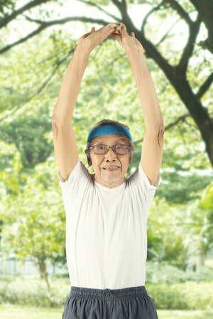 Portrait of an elderly man wearing sportswear while stretching his arm in the park