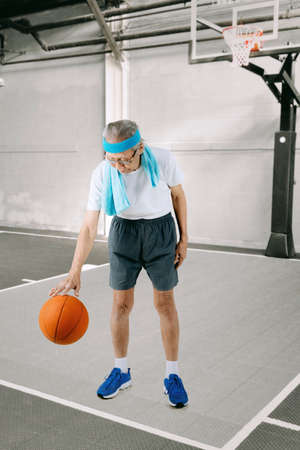 Portrait of an elderly man wearing sportswear while dribbling a basketball in the stadium