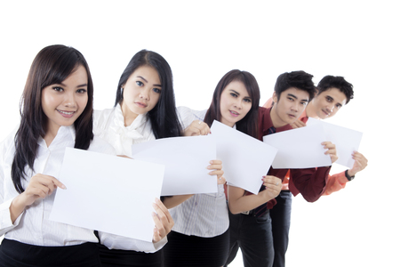 Young business team showing empty papers and looking at the camera, isolated on white background Stock Photo