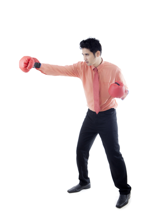 Side view of a young businessman wearing boxing gloves while punching something, isolated on white background