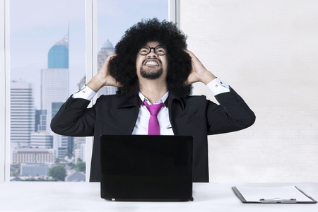 Afro businessman looks stressful while sitting near the window with a laptop and clipboard on the desk Stock Photo