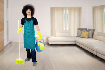 Image of an Afro maid holding a broom and bucket while standing in the living room