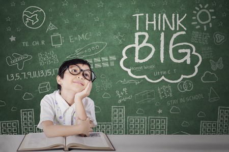 Photo of cute girl studying with a book while looking at a text of think big on the chalkboard Stock Photo