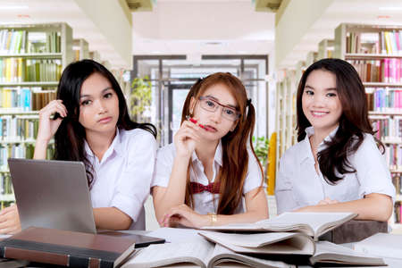 Three pretty female high school students sitting in the library and smiling at the camera with books and laptop on the table