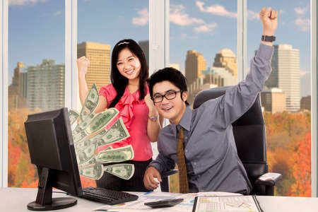 Portrait of Asian business people feels happy while working together with money on the computer screen