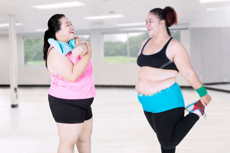 Two obese women doing stretching in the fitness center while smiling together Stock Photo