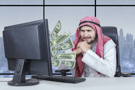 Portrait of Arabian businessman feeling unhappy while looking at money on the monitor with winter background on the window
