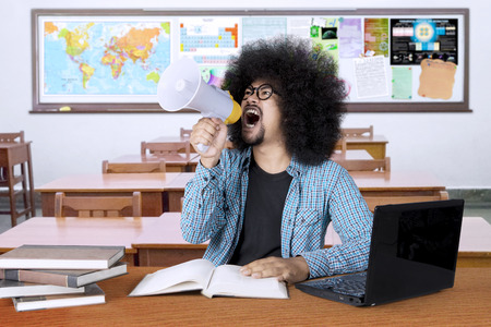 Picture of a male college student looks angry and screams on a megaphone while learning in the classroom Stock Photo