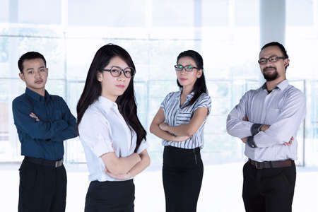 Group of confident multiracial business people looking at camera with arms crossed and standing in the office