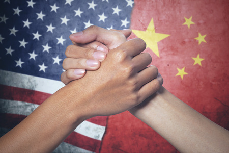 Concept of peace. two hands people posing partnership with China and United States flag in the background Stock Photo