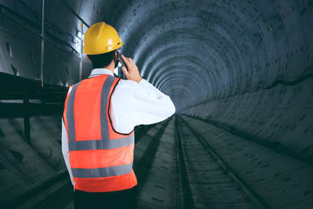 Back view of young engineer speaking on a mobile phone while standing in the underground tunnel