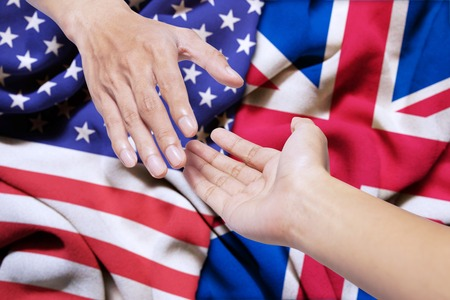 Symbolizing of peace. Hand of United states offering a help with hand of England Stock Photo