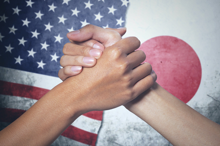 Closeup of two hands people posing partnership with Japan and United States flag in the background