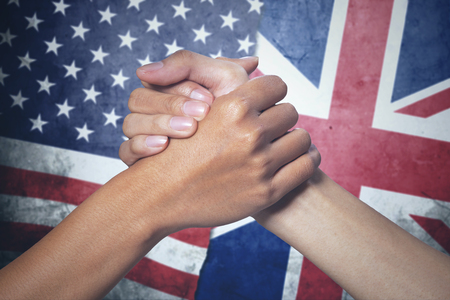 Concept of peace. Two hands of people posing partnership with England and United States flag in the background