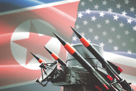 Concept of conflict. Nuclear weapon of mass destruction with North Korea and USA flag in the background