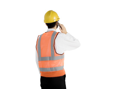 Back view of young engineer speaking on a mobile phone and standing in the studio, isolated on white background Stock Photo