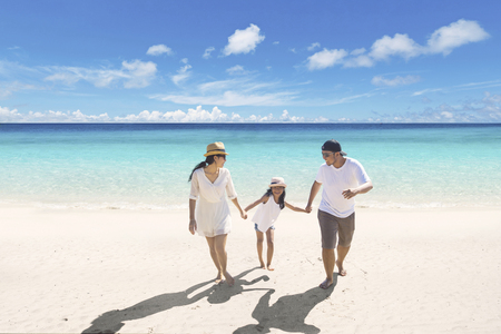 Young parents having a holiday with their daughter while walking in the tropical beach