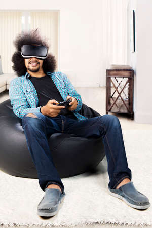 Portrait of Afro man using virtual reality glasses and joystick for play video game while sitting at home