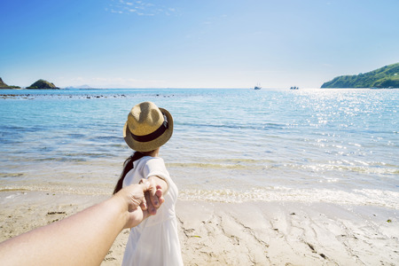 Back view of Asian woman holding hand of her boyfriend while leading to the beach Stock Photo