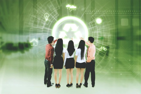 Back view of business people touching a symbol of recycle on the virtual screen Stock Photo