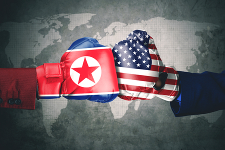 Concept of conflict. Two hands wearing boxing gloves with North Korea and USA flag Stock Photo