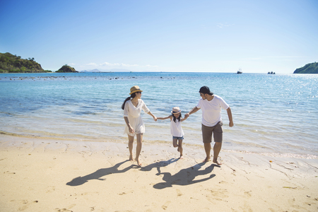 Image of young parents running on the beach while holding their hands daughter