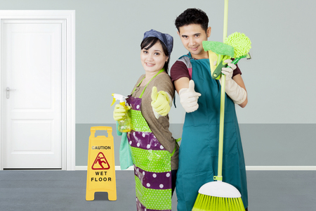 Image of two janitors showing thumbs up while standing with cleaning equipment in the hotel Stock Photo